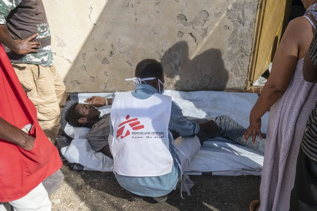 Een medewerker in het Al Hashaba transitie kamp helpt een patiënt.