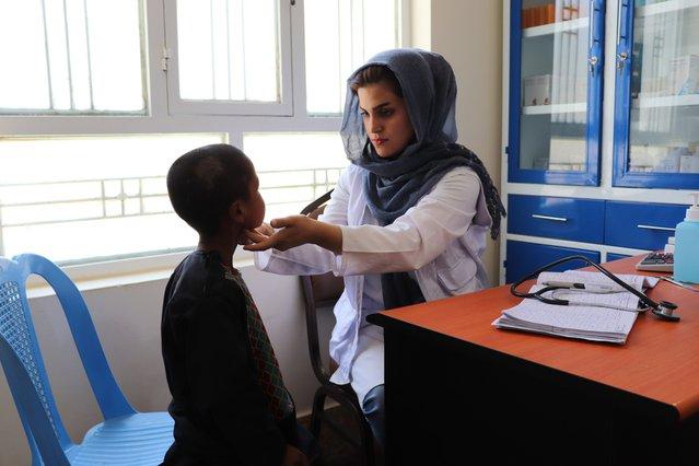 Een kind krijgt een consult van onze arts Azada Barez in Herat, Afghanistan.