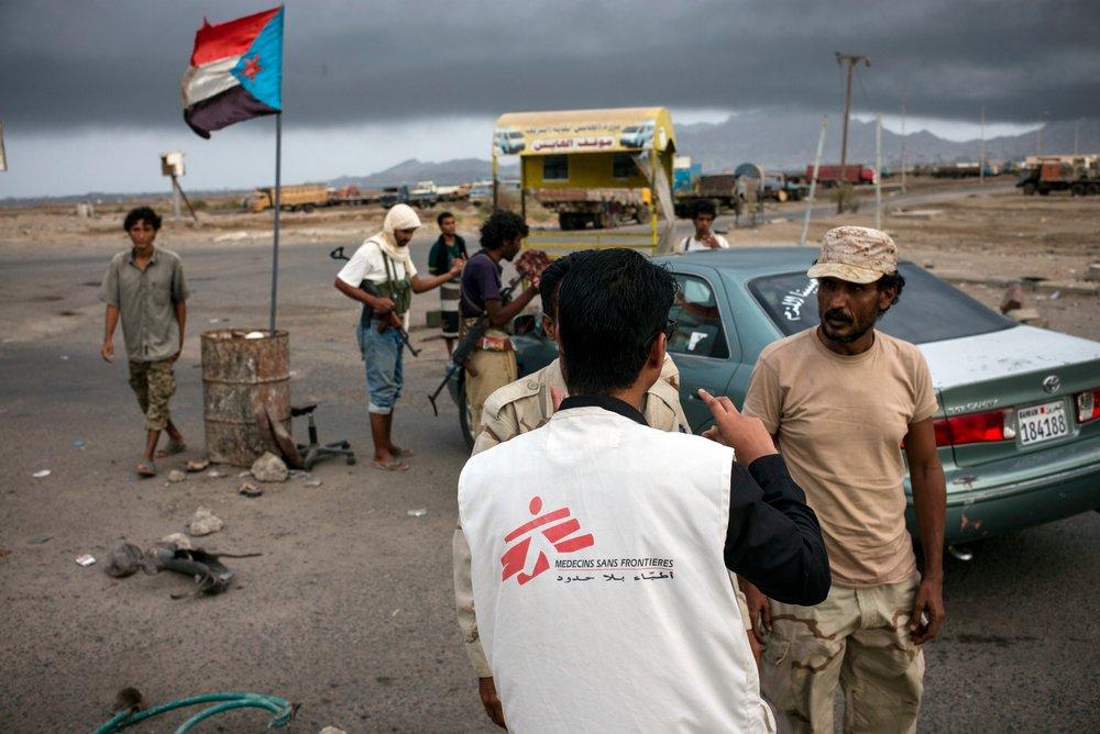 Een medewerker spreekt met gewapende mannen bij een checkpoint in Aden, Jemen, jui 2015. ©Guillaume Binet/MYOP