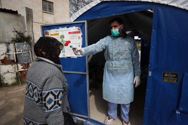 Een arts controleert de temperatuur van een patiënt bij een ziekenhuis in het noorden van Syrië dat door ons ondersteund wordt.